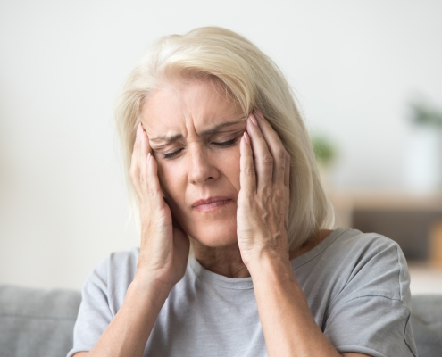 upset older woman with a headache